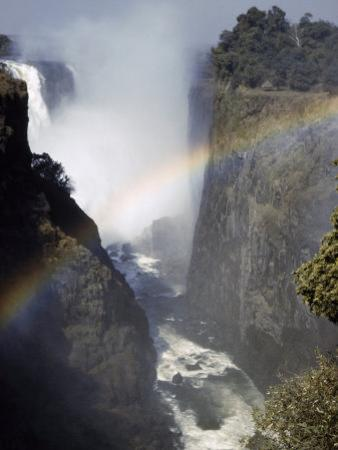 Rainbow Spans Gorge Below Victoria Falls, Mist Rises from Falls