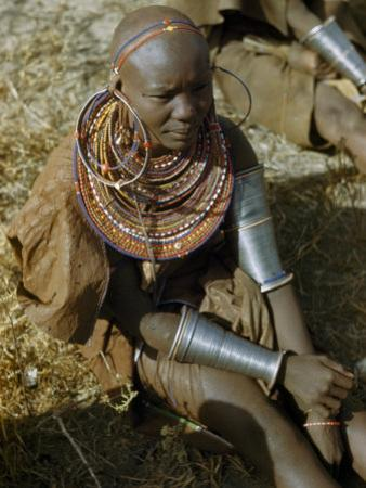 Seated Masai Woman Wears Large Arm Bands, Necklaces, and Earrings