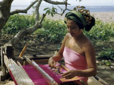 Woman Sitting under a Frangipani Tree Weaves at a Loom