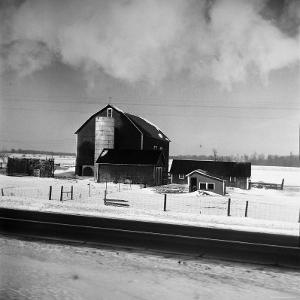 Barn and Farm Buildings in Snow, as Seen from Train Window by Walker Evans