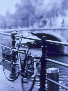 Bicycle on Rail by Canal, Amsterdam, Netherlands by Walter Bibikow