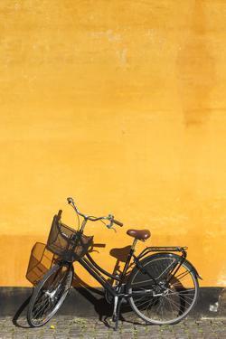 Denmark, Zealand, Copenhagen, Yellow Building Detail with Bicycle by Walter Bibikow