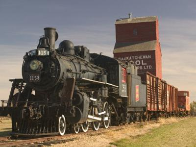 Steam Train and Grain Elevator in Western Development Museum, Saskatchewan, Canada by Walter Bibikow