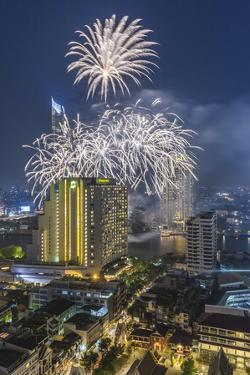 Thailand, Bangkok. Riverside, high angle skyline view with fireworks at dusk. by Walter Bibikow