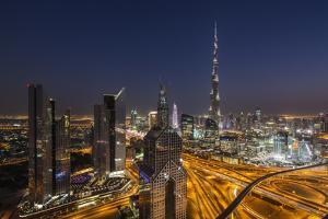 UAE, Downtown Dubai. Cityscape with Burj Khalifa at night. by Walter Bibikow