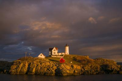 USA, Maine, York Beach, Nubble Light Lighthouse with Christmas decorations, sunset by Walter Bibikow