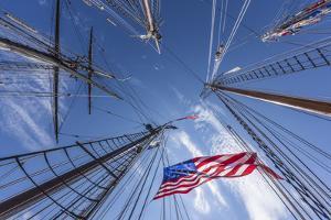 USA, Massachusetts, Cape Ann, Gloucester. Gloucester Schooner Festival, schooner masts and US flag. by Walter Bibikow