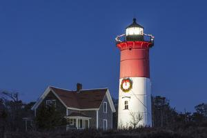 USA, Massachusetts, Cape Cod, Eastham. Nauset Light with Christmas wreath at dawn. by Walter Bibikow