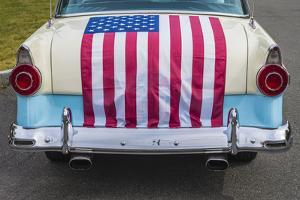 USA, Massachusetts, Essex. Antique cars, detail of 1950's-era Ford draped with US flag by Walter Bibikow