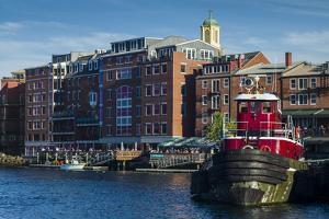 USA, New Hampshire, Portsmouth, waterfront buildings with tugboat by Walter Bibikow