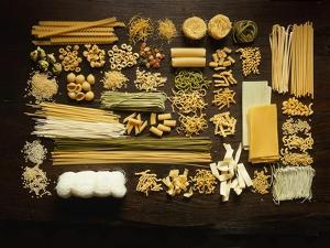 Many Different Types of Pasta on Dark Wooden Background by Walter Cimbal
