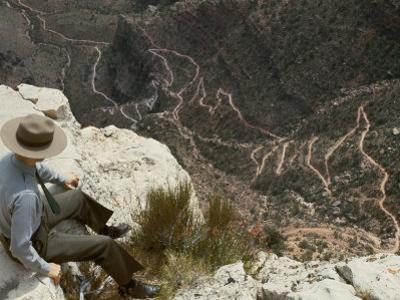 A Park Ranger Views a Twisting Hiking Trail from High Above