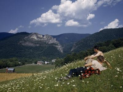 Men in Flower-Carpeted Hillside Meadow Look Toward Seneca Rocks