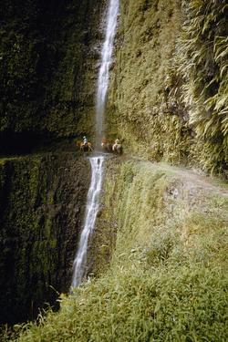 Riders Duck Behind a Waterfall on an Impossibly Narrow Cliff Trail by Walter Meayers Edwards