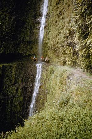 Riders Duck Behind a Waterfall on an Impossibly Narrow Cliff Trail