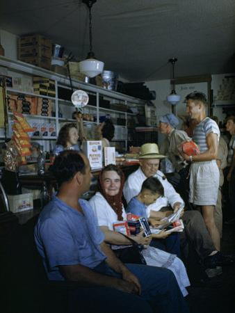 Townsfolk Linger and Shoppers Shop at a General Store