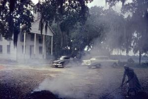 A Woman Rakes and Burns Brush in Front of a Church on Edisto Island, South Carolina, 1956 by Walter Sanders