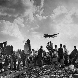 US C-47 Cargo Plane Flying over Ruins, Approaching Tempelhof Airport with Food and Supplies by Walter Sanders