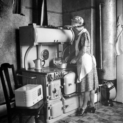 Woman Cooking on Old Fashioned Stove by Walter Sanders