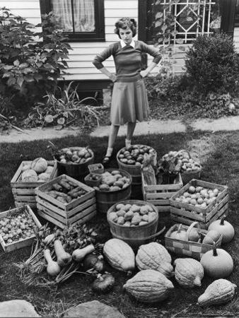 Woman Looking at Victory Garden Harvest Sitting on Lawn, Waiting to Be Stored Away for Winter by Walter Sanders