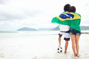 Brazil Soccer Fans Stand on Beach Together with Flag for World Cup with Ball by warrengoldswain