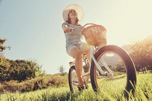 Carefree Woman Riding Bicycle in Park Having Fun on Summer Afternoon by warrengoldswain