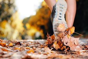 Close up of Feet of a Runner Running in Autumn Leaves Training for Marathon and Fitness Healthy Lif by warrengoldswain