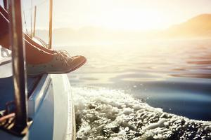 Feet on Boat Sailing at Sunrise Lifestyle by warrengoldswain