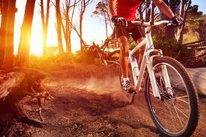 Mountain Bike Cyclist Riding Single Track at Sunrise Healthy Lifestyle Active Athlete Doing Sport by warrengoldswain