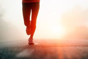 Runner Feet Running on Road Closeup on Shoe. Woman Fitness Sunrise Jog Workout Welness Concept. by warrengoldswain