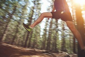 Runner Jumping on Trail Run in Forest for Marathon Fitness by warrengoldswain