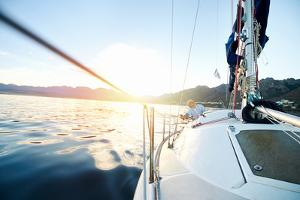 Sailing Boat on on Ocean Water at Sunrise with Flare and Outdoor Lifestyle by warrengoldswain