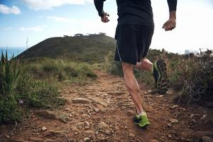 Trail Running Athlete Exercising for Fitness and Health Outdoors on Mountain Pathway by warrengoldswain