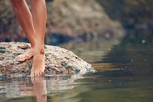 Woman on Rock at Beach Dipping Toes in Water, Having Fun Outdoor Lifestyle by warrengoldswain