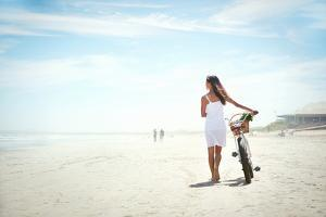 Woman Walking with Bicycle along Beach Sand Summer Lifestyle Carefree by warrengoldswain
