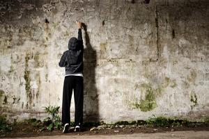 Youngster with Spray Paint and an Empty Wall for Graffiti by warrengoldswain