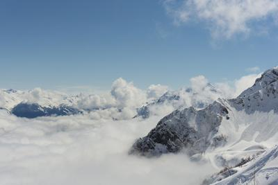 View on Winter Snowy Mountains and Blue Sky above Clouds, Krasnaya Polyana, Sochi, Russia