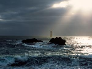 Waves breaking on coast with Nividic Lighthouse in the background, Ushant Island, Finistere, Bri...