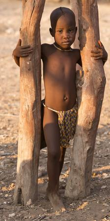 Namibia, Opuwo. Young Himba child in late afternoon light.