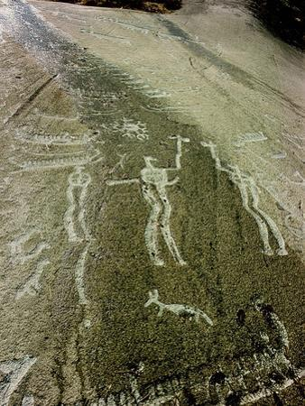 Petroglyph with two men facing each other and brandishing axes, Bronze Age by Werner Forman