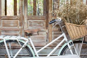 Bicycle with a Basket of a Dried Bouquet Flower Stand in Front of Wooden and Rustic House Backgroun by WichitS