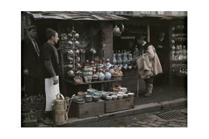 A Bulgar Inspects Pottery as an Albanian Boza Vendor (Left) Looks On by Wilhelm Tobien