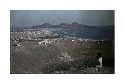 A Man Sits Atop a Hill, Overlooking the Port Built on the Isleta