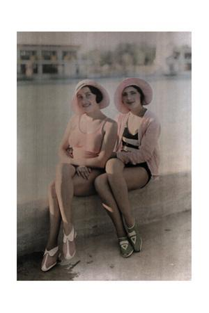 Two Girls in Bathing Suits Sit on a Concrete Ledge