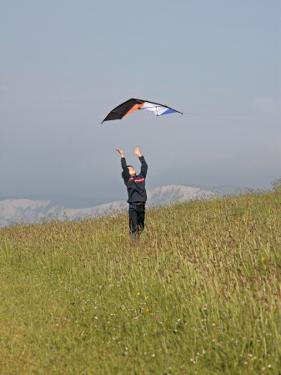 England, Isle of Wight; Boy Flying a Kite on the Downs Near Compton Bay in Southwest of the Island by Will Gray