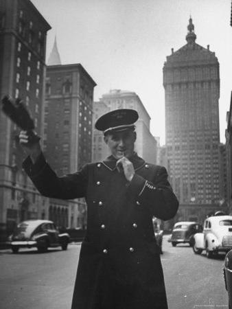 Park Avenue Doorman Using Whistle to Flag Down a Taxi For One of the Residents of His Building