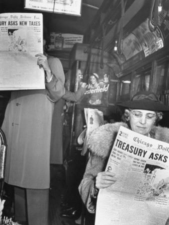 People Reading Tribune Newspaper on Train
