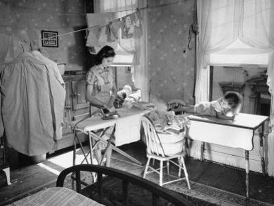 Woman Ironing in Slum Home