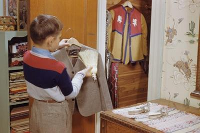 Boy Brushing His Suit Jacket by William P. Gottlieb