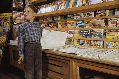 Boy Holding Paper in Newsstand by William P. Gottlieb